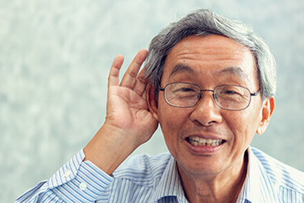 eldery person with hands on his ears who has trouble hearing
